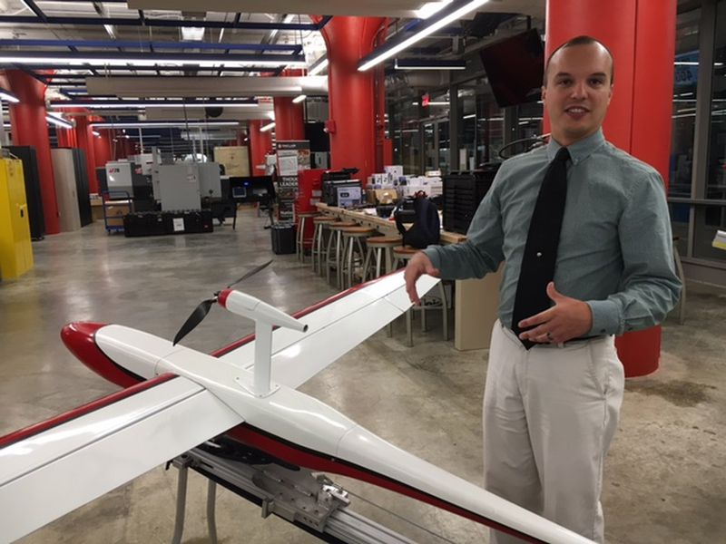 In this 2017 file photo, Andrew Shepherd, who heads Sinclair Community College's unmanned aerial vehicles program, stands next to a version of Unmanned Solutions Technology's Pelican II fixed-wing UAV. THOMAS GNAU/STAFF