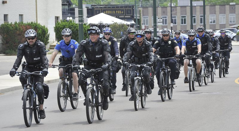 Dayton police ride bikes alongside protesters on Wayne Ave. Saturday to protect them as they march for George Floyd. MARSHALL GORBYSTAFF