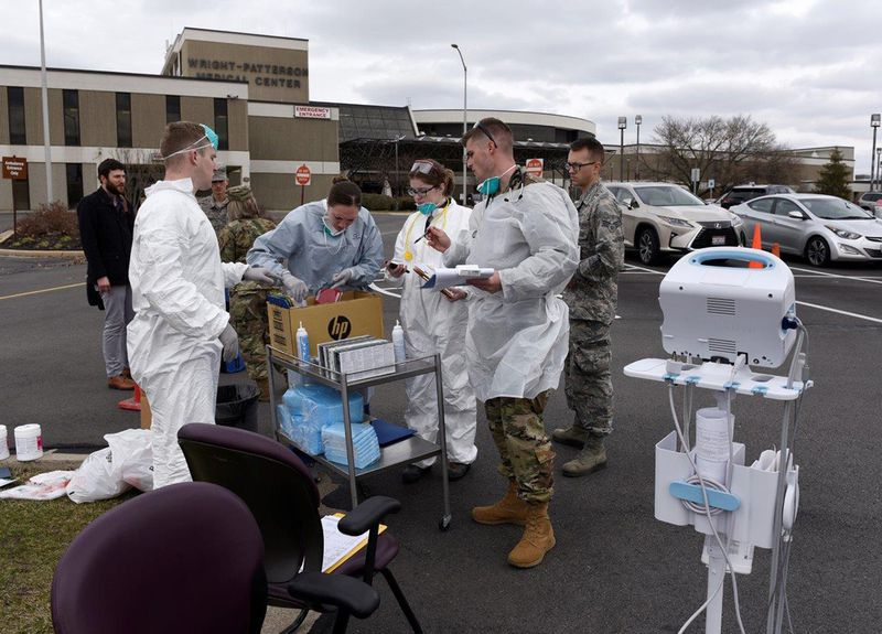 Air Force personnel prepare to screen patients in front of the Wright-Patterson Medical Center March 16. The 88th Medical Group staff began screening patients before they entered the medical center as part of the COVID-19 protocol instituted at the facility. U.S. AIR FORCE PHOTO/TY GREENLEES