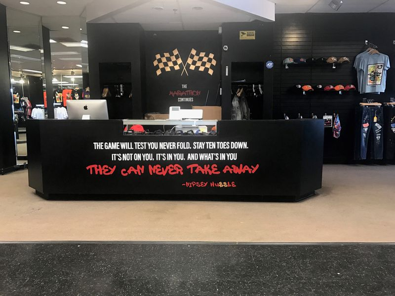 One of the inspirational sayings of Nipsey Hussle is highlighted on the on the counter of the stylish 48th Clothing store in the Northwest Plaza. Tom Archdeacon/STAFF