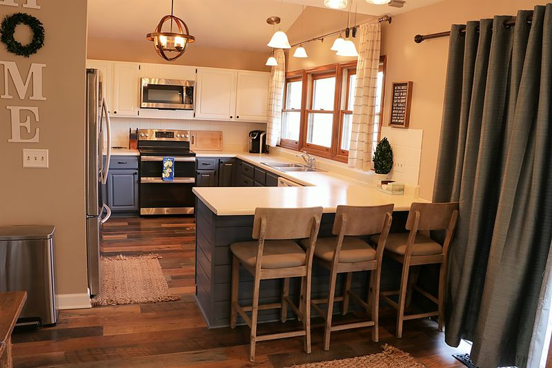The kitchen and breakfast room were updated with wood-laminate flooring, painted cabinetry, appliances and lighting. A sliding patio door opens from the breakfast room to the rear deck and patio. CONTRIBUTED PHOTO BY KATHY TYLER