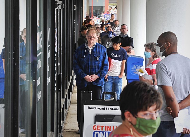 A crowd gathers  before the Moraine BMV office reopened Tuesday, May 26, 2020, after being closed due to the coronavirus pandemic. MARSHALL GORBY/STAFF