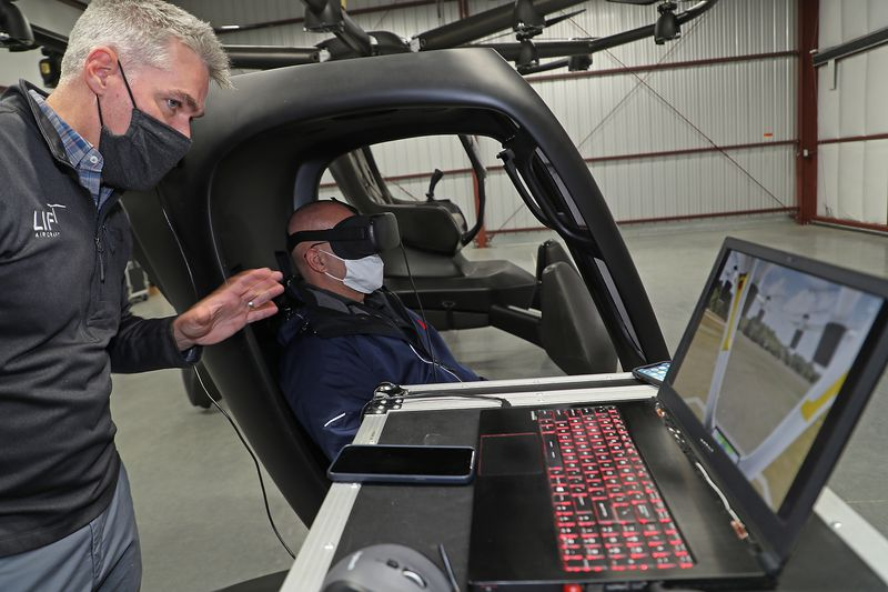 """Matthew Chasen, CEO of LIFT Aircraft, instructs a member of the media on how to fly a simulator for LIFT Aircraft's electric vertical takeoff and landing (eVTOL) vehicle at Springfield-Beckley Municipal Airport Friday. The """"flying car"""" is the first to arrive in Ohio, and is supported by a recent $226,000 grant from JobsOhio's Ohio Site Inventory Program in infrastructure investments at Springfield-Beckley Municipal Airport. BILL LACKEY/STAFF"""