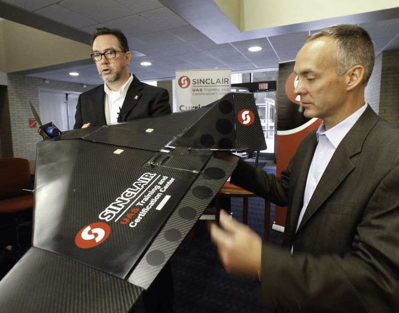 Sinclair Community College President Steve Johnson, left, and Jeff Hoagland, president and CEO of the Dayton Development Coalition, discuss Sinclair's recently announced $1.4 million investment in an Unmanned Aerial Systems Program. CHRIS STEWART / STAFF